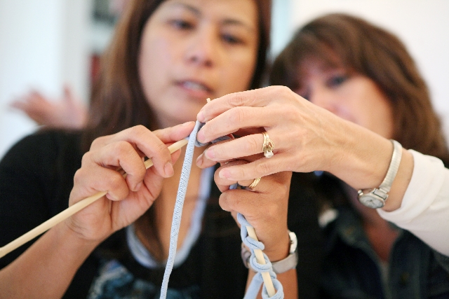 """Ami Vaughn, left, watches as Gwen Campbell knits with T-shirt """"yarn"""" during REcycled Knitting class at Selah art salon. The workshop, led by Alison Turner, aimed to teach people to kni ..."""