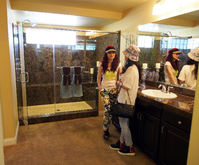 Yanie Tang, left, and Kenan Zhang talk about the master bathroom in a model home at an American West's Reserve at the Coronado Ranch subdivision.