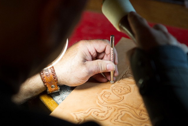 "Steve Gilworth works on the details of a leather road case insert. He calls his braiding work ""Zen-like, like meditation."""