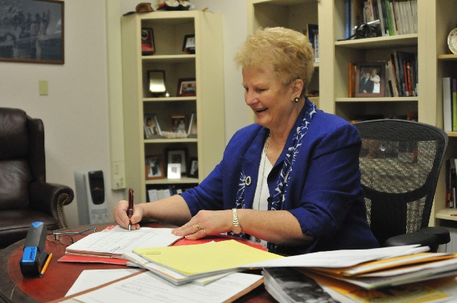 Sandra Ransel signs off on students' graduation records April 9 at Desert Rose Adult High School, 444 W. Brooks Ave. Ransel underwent brain surgery in the fall to alleviate the symptoms of her Par ...