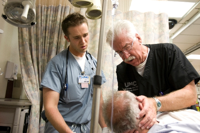 University Medical Center medical student Brandon Crum, left, watches as Dr. Dale Carrison, UMC's head of emergency services, checks a patient in August 2009. Carrison, former head of the Ne ...