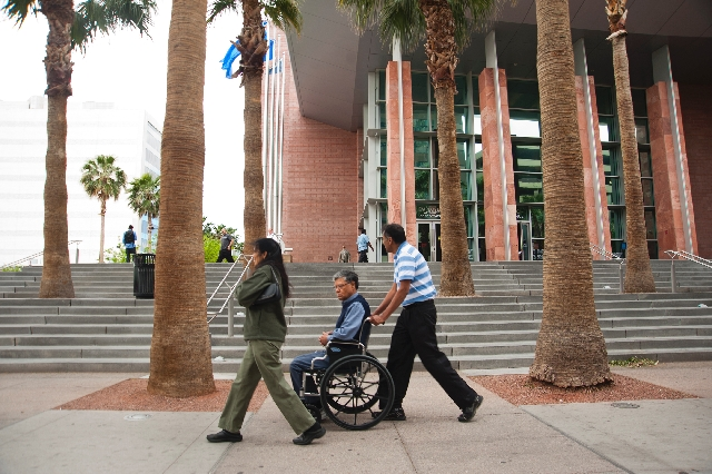Dr. Dipak Desai, center in the wheelchair, leaves the Regional Justice Center with family members after his hearing in a criminal case stemming from the hepatitis C outbreak, in downtown Las Vegas ...