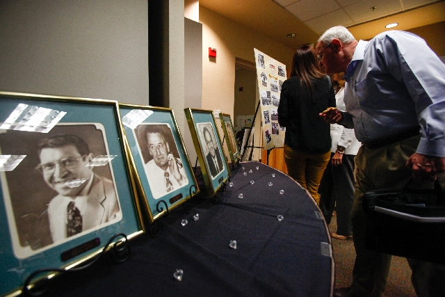 People browse through displays of past Henderson mayors and poster boards of photos representing each decade since the city's official incorporation 60 years ago on April 16, 1953, after a s ...