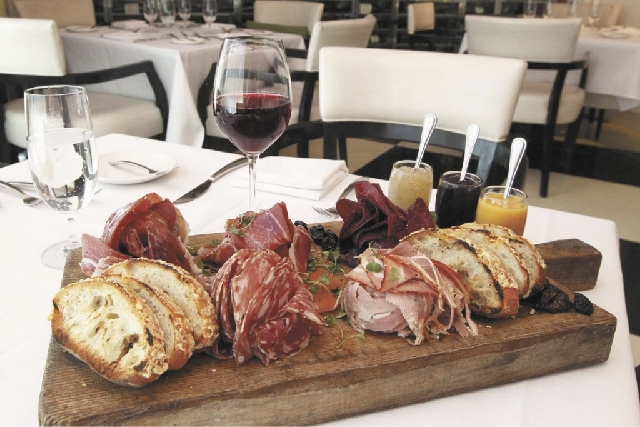 A charcuterie tray from Vintner Grill features, top row from left, La Quercia Speck prosciutto, prosciutto San Daniele and Bresaola Citterio; front row, crostini bread flanks Fra Mani Salumi Tusca ...