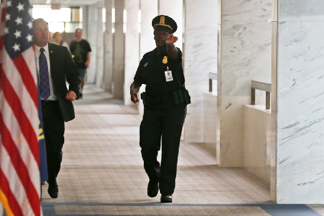 A Capitol police officer tells people to clear the hallway on the third floor of the Hart Senate Office building after reports of suspicious packages discovered on Capitol Hill in Washington on We ...