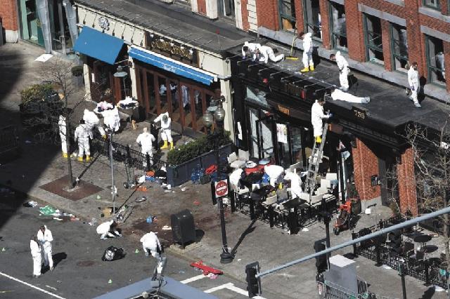 Investigators Wednesday comb through the scene of one of the blast sites of the Boston Marathon explosions.