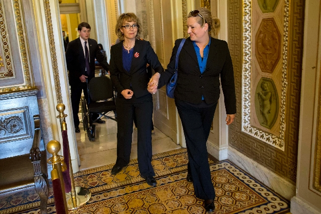 Former Arizona Rep. Gabrielle Giffords, center, is escorted in the hallway outside the Senate Chamber on Capitol Hill in Washington on Wednesday before the start of a Senate vote on gun control le ...