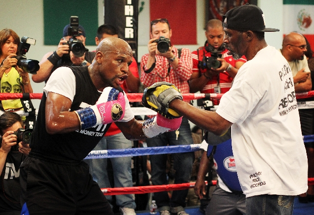 Trainer Roger Mayweather, right, works out nephew Floyd Mayweather Jr. in preparation for his May 4 fight against Robert Guerrero. The media was invited Wednesday into the Mayweather Boxing Club i ...