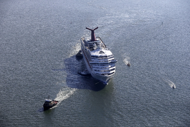 The disabled Carnival Lines cruise ship Triumph is seen being towed to harbor off Mobile Bay, Ala., in 2013. Carnival Cruise Lines on Wednesday announced a $300 million program to add emergency ge ...