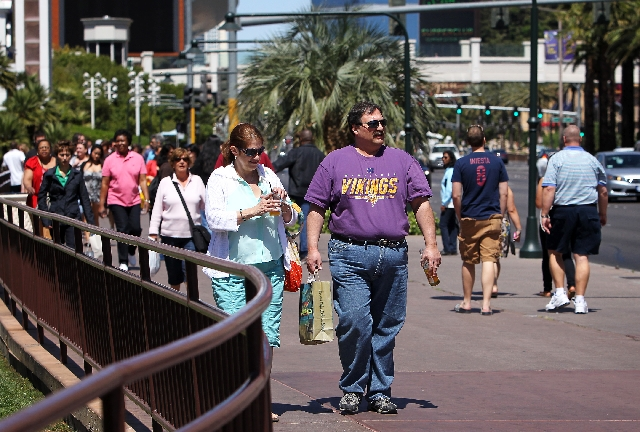 Steve Vick, middle, walks with his wife Pam Vick down the Las Vegas Strip with a beer bottle on Thursday. According to Vick, he asked for a to-go cup and his bartender at Señor Frogs told h ...