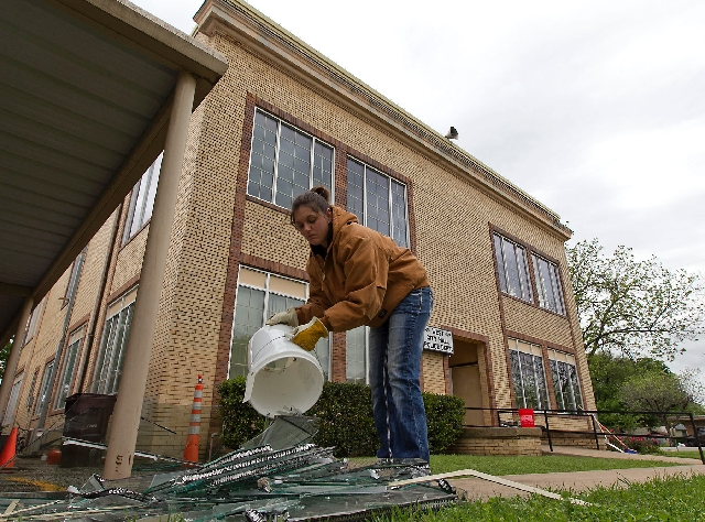 Natassia Browning, of West, who lives a half mile from the West Fertilizer Co., helps clean up broken glass at the West City Hall and Police Department caused by Wednesday night's explosion in Wes ...