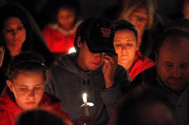 People comfort one another during a candle light vigil at St. Mary, Church of the Assumption for victims, families, friends and first responders involved with the recent fertilizer plant explosion ...
