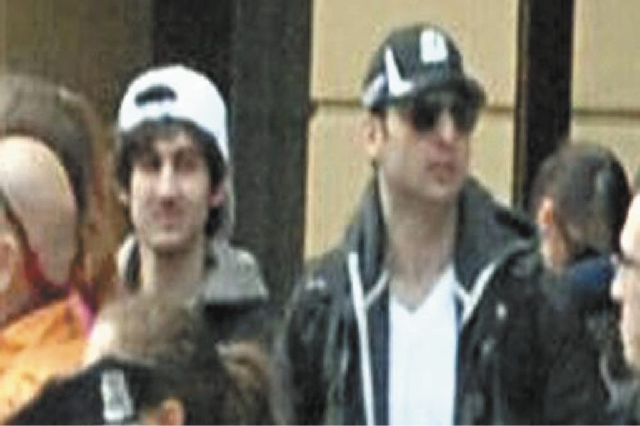 """This photo released by the FBI early Friday shows the Boston Marathon bombing suspects together, walking through the crowd in Boston on Monday before the explosions at the Boston Marathon. """"Suspec ..."""