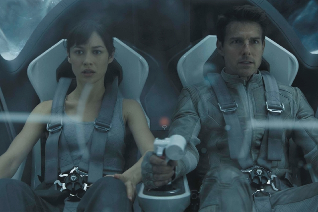 "Olga Kurylenko, as a mysterious stranger who crash lands on a ruined Earth, and Tom Cruise, as security repairman Jack Harper, appear in a scene from ""Oblivion."""