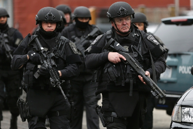 Police in tactical gear conduct a search for a suspect in the Boston Marathon bombings Friday in Watertown, Mass. Dozens of officers and National Guard members are in Watertown, where gunfire and  ...