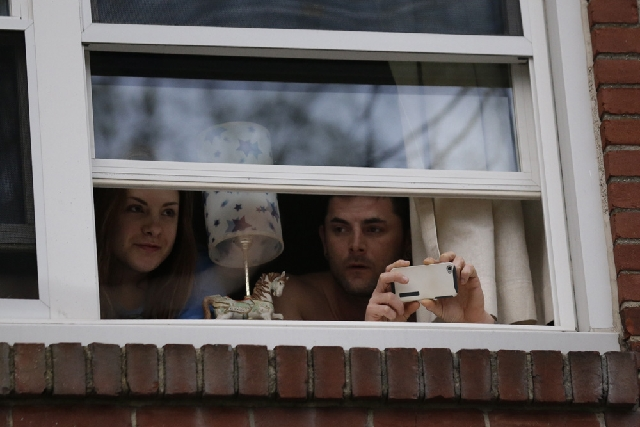 Residents look out a window as officials inspect an apartment building in Watertown, Mass., on Friday. Dozens of officers and National Guard members are in Watertown, where gunfire and explosions  ...