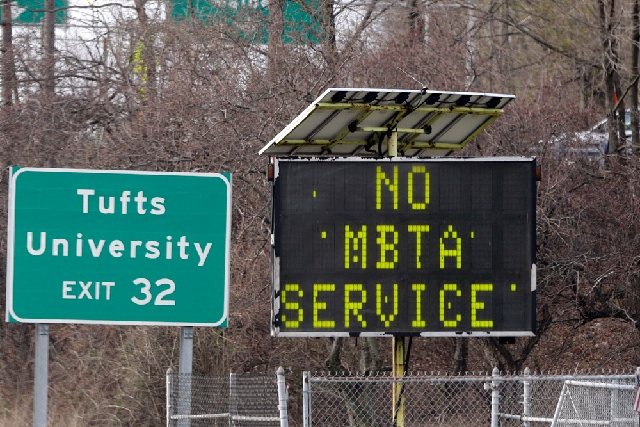 A sign along I-93 in Medford, Mass. announces no MBTA service on Friday. Two suspects in the Boston Marathon bombing killed an MIT police officer, injured a transit officer in a firefight and thre ...