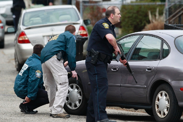 Police surround a home while searching for a suspect in the Boston Marathon bombings in Watertown, Mass., on Friday.  The two suspects in the Boston Marathon bombing killed an MIT police officer a ...