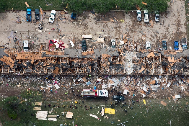 In this aerial photo, law enforcement and rescue personnel search the damage to an apartment complex from the explosion of the West Fertilizer plant on Thursday in West, Texas. A massive explosion ...