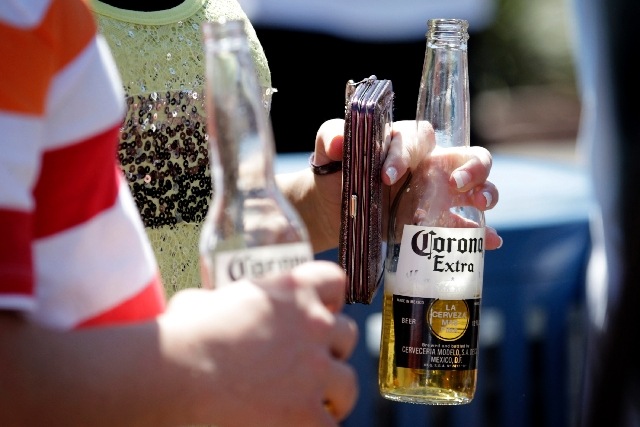 Strip-goers carry glass bottles on the Strip in Las Vegas on Thursday. County commissioners have ordered staff to develop an ordinance banning glass bottles on the Strip.