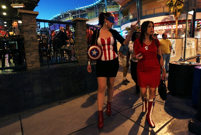 Necole Zeigler, right, wearing Wonder Woman boots for 40 days to help raise money for Child Abuse Prevention and Awareness month, walks with Kyla Vivier, in her take on Captain America, while maki ...