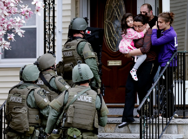 Family members leave their home as a SWAT team searching for a suspect in the Boston Marathon bombings enters the building Friday in Watertown, Mass. During the search, Boston area officials had s ...
