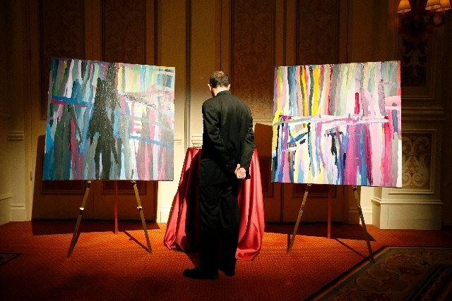 A man looks at paintings in a silent auction during a fundraiser for Opportunity Village at The Venetian. About $300,000 was raised during the event. The proceeds will help fund scholarships for i ...