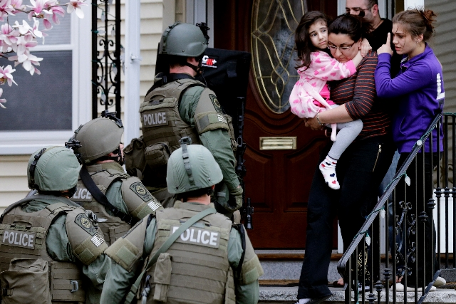 A woman carries a girl from their home as a SWAT team searching for a suspect in the Boston Marathon bombings enters the building in Watertown, Mass., on Friday. Two suspects in the Boston Maratho ...