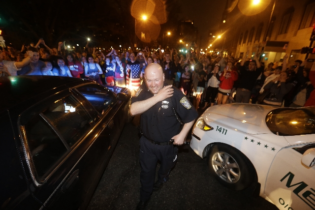 A police officer reacts to news of Friday night's arrest of one of the Boston Marathon bombing suspects. Dzhokhar Tsarnaev, 19, was captured in Watertown, Mass., after a manhunt that left the city ...