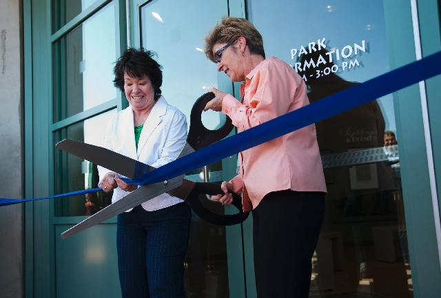 Clark County Commissioners, from left, Mary Beth Scow and Chris Giunchigliani cut the ribbon during the grand opening and dedication of the new Nature Center at the Clark County Wetlands Park on S ...