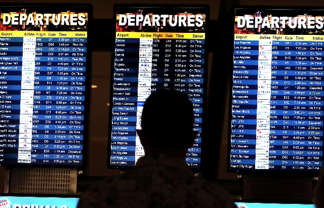 A man studies the flight board inside Terminal 3 at McCarran International Airport. Reports on www.flightstats.com indicated moderate delays at 2 p.m. Tuesday for Las Vegas passengers.
