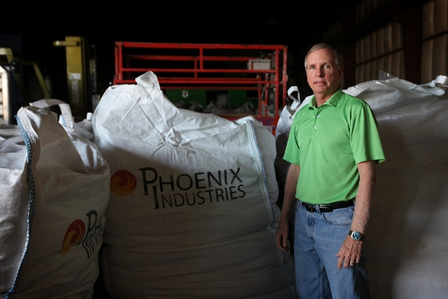 Kelly R. Sockwell, executive vice president and director of operations at Phoenix Industries LLC in North Las Vegas, stands next to bags of pelletized asphalt that are ready to be exported to Brazil.