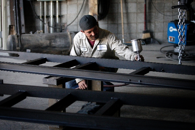 Rudolfo Robles of North Las Vegas paints a component to a feed system used in pelletized asphalt rubber technology at Phoenix Industries LLC. The company was one of five local businesses to partic ...