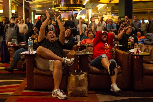 Ravens fan Shannon Goo of Honolulu, Hawaii, left, cheers as his friend, 49ers fan Ramsey Gaspar of Las Vegas, reacts, during the Super Bowl in the sports book at Red Rock Resort in Las Vegas on Fe ...