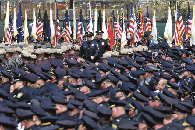 Police officers arrive for a memorial service Wednesday for fallen Massachusetts Institute of Technology campus officer Sean Collier on the MIT campus in Cambridge. Authorities say Collier was kil ...