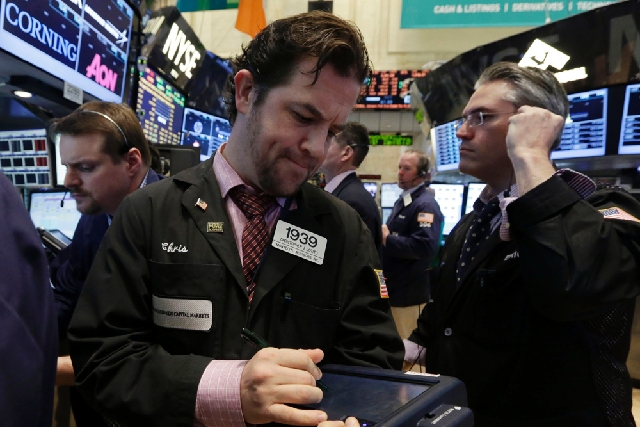 Trader Christopher Lotito, center, works on the floor of the New York Stock Exchange on Wednesday. No sooner did a phony Associated Press report of explosions at the White House appear on Twitter  ...