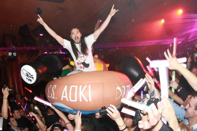 DJ Steve Aoki does some crowd-surfing while riding on top of a raft at Surrender nightclub at Wynn Las Vegas in January, 2013.