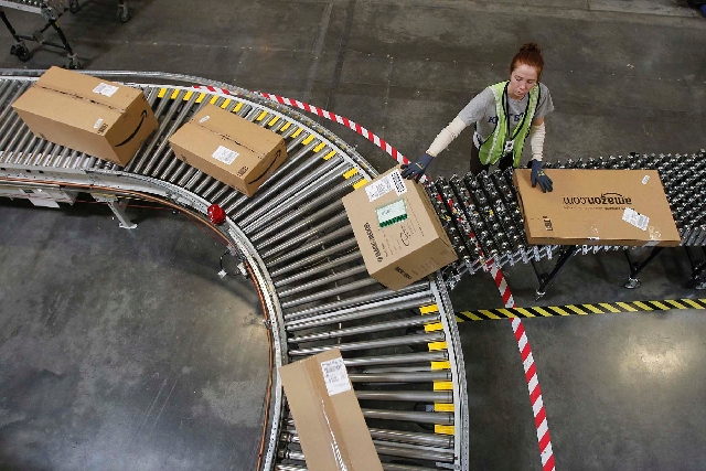 Katherine Braun sorts packages toward the right shipping area at an Amazon.com fulfillment center, in Goodyear, Ariz., in the 2010 file photo. Amazon.com supports the move to impose state and loca ...
