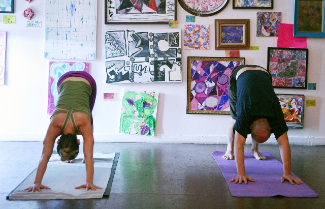 Olga Samoilova, left, and Larry Lee participate in a candlelight yoga class on Thursday at BlueSky Yoga inside the Arts Factory in Las Vegas. Classes are based upon donation, and students are enco ...