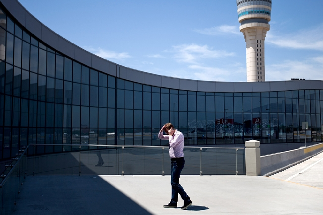 The control tower stands in the background as a passenger paces while on the phone outside the international terminal at Hartsfield-Jackson airport Friday in Atlanta. The Federal Aviation Administ ...
