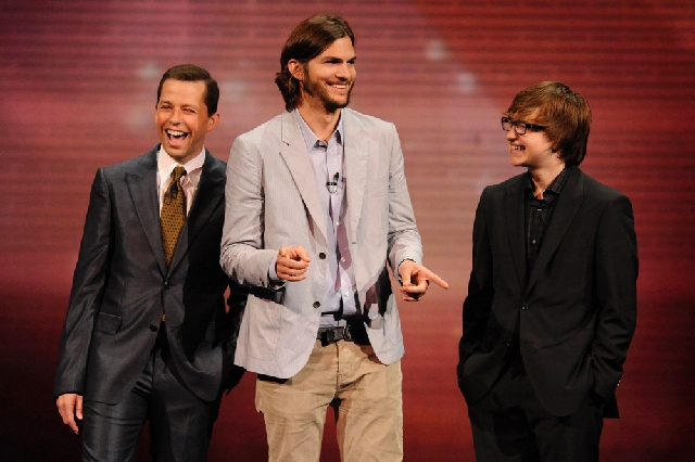 """In this May 18, 2011, publicity image released by CBS, the cast of """"Two and a Half Men,"""" from left, Jon Cryer, Ashton Kutcher, and Angus T. Jones are shown during their presentation at CBS' Upfron ..."""