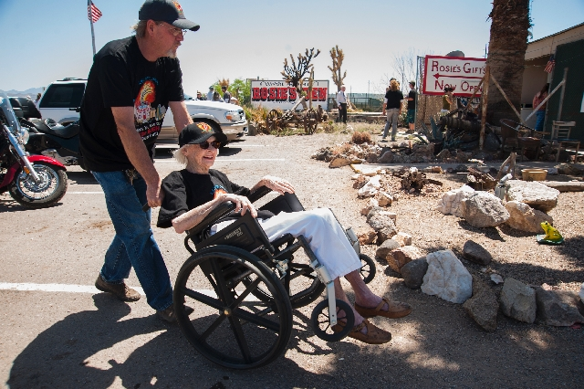 Rose Larsen, 87, the owner of Rosie's Den, is wheeled around by her son, Hitch Larsen, on Saturday during the groundbreaking for her cafe, after it burned down more than a year ago, at 19949 N. U. ...