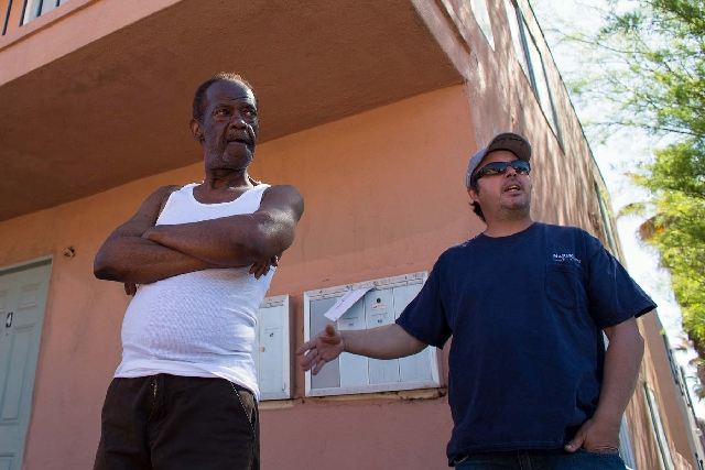 Tenant Dennis Walston, left, listens as his landlord, Malcolm Perez, talks about the money owed to Las Vegas by the homeowners association for a three-building condominium complex on Silver Dollar ...