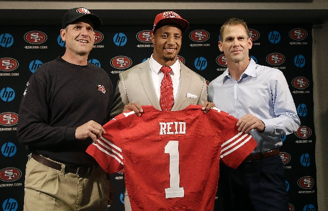 Coach Jim Harbaugh, left, general manager Trent Baalke, right, and the San Francisco 49ers had perhaps the best NFL Draft, topped by the selection of Louisiana State safety Eric Reid, center, in t ...