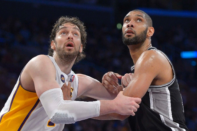 Los Angeles Lakers forward Pau Gasol, and San Antonio Spurs forward Tim Duncan battle for a rebound during the second half in Game 4 of a first-round NBA basketball playoff series on Sunday. The S ...