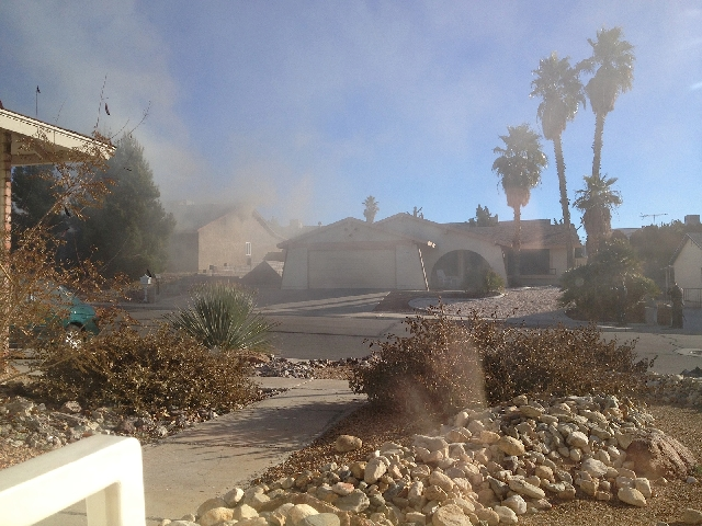 In a view from across the street, police and firefighters respond to a fire at 1313 Esther Drive in Boulder City on Monday. Authorities are investigating reports of a homicide and a fire at the ho ...