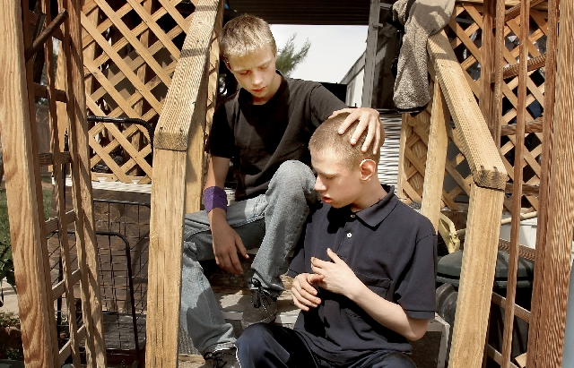 Draven Avila, 16, left with his brother Geovanny, 14, sits on the steps of a neighbor's home on Tuesday. Draven help saved his autistic brother after an early morning fire that destroyed the famil ...