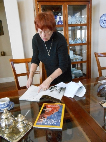 Barbara Harff looks through the November 2003 issue of Atlantic Monthly in which her work on genocide studies received recognition. The National Geographic on the table, dated January 2006, also u ...