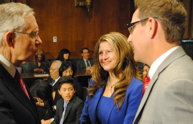 Jennifer Dorsey, a partner at the Las Vegas firm of Kemp, Jones & Coulthard and her husband Daron Dorsey, right, are greeted by Sen. Harry Reid, D-Nev. The Senate Judiciary Committee voted along p ...
