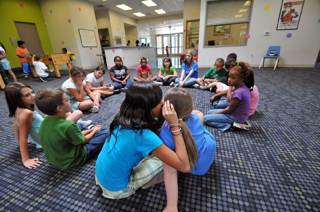 """Destiny Sanchez, 10, whispers a secret phrase to 8-year-old Alissa Salazar during a game of """"telephone"""" June 13, 2011, at the Boys and Girls Clubs of Henderson's John C. Kish unit, 401 Drake St. T ..."""